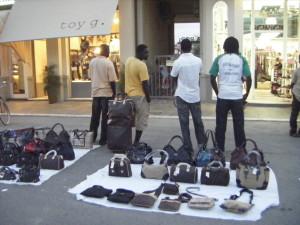 """Alcuni venditori ambulanti con la loro """"merce"""" davanti ai negozi"""